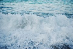 Close-up photo of waves crashing on the sand shore. / Stock Photography