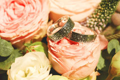 Close up photo of wedding rings on pink rose Stock Photos