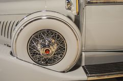 Detail of a white classic car spare tire. A close up photo of a white classic car showing side spare tire and part of the door stock photo