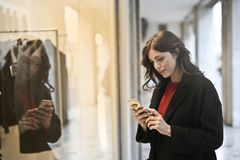 Close-up Photo of Woman in Black Coat Using Smartphone Stock Photos