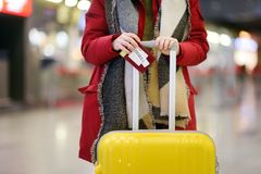 Close-up photo of woman holding passport and boarding pass at the international airport. Close-up photo of woman with yellow suitcase holding passport and royalty free stock images