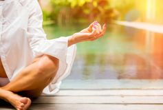 Close up photo of woman practicing yoga and sitting in lotus pose royalty free stock photography