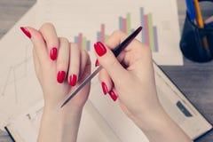 Close up photo of woman`s hand correcting fingernail using nail stock images