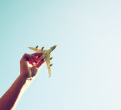 Close up photo of woman's hand holding toy airplane against blue sky with clouds.  Royalty Free Stock Photography