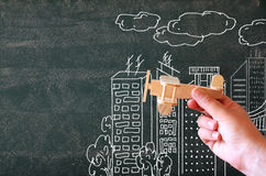 Close up photo of woman's hand holding wooden toy airplane against chalkboard with city illustration. Success and inspiration concept Royalty Free Stock Photos