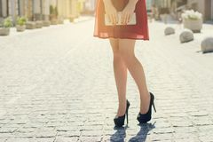 Close up photo of woman`s long legs view of city red dress black royalty free stock image