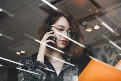 Close-up photo of woman talking on phone with director of development in evening office and holding folder with documents. royalty free stock images