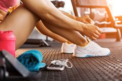 Woman tying trainers in the gym close up royalty free stock photo