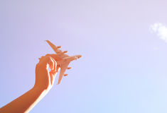 Close up photo of womans hand holding toy airplane against blue sky with clouds.  Stock Images