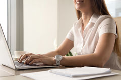 Close up photo of womans hands typing on laptop. Smiling woman working on computer. Female office worker doing daily routine. Workplace ergonomics and correct Stock Photography