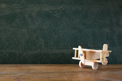 Close up photo of wooden toy airplane against chalkboard Royalty Free Stock Images