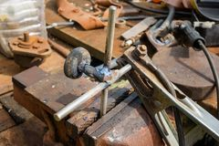 Homemade tool for repair. manufacture by own hands of the tool from iron. welding of metals. Close up photo of worker hand using sandpaper on metal workpiece Stock Images