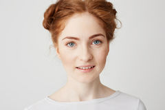 Close up photo of young beautiful redhead girl with buns looking at camera smiling over white background. Royalty Free Stock Photos