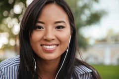 Close-up photo of young cheerful asian woman listening to music, Stock Photography