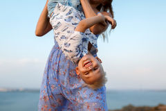 Close-up photo of a lovely woman playing with her cute son on a blurred nature background. Outdoors. Copy space. royalty free stock image