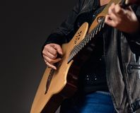 Close-up of the guitar player hands. Close up photo of young musician playing on the acoustic guitar Royalty Free Stock Image