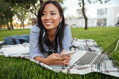 Close-up photo of young smiling asian female student listening t Stock Photo