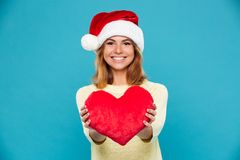 Close-up photo of young smiling brunette woman in Santa`s hat holding soft red heart, looking at camera. Isolated over blue background Royalty Free Stock Photography