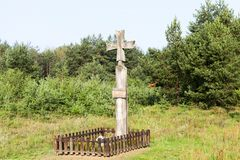 Religious wooden cross. Close-up photograph of a wooden religious Christian cross set near a forest. Blue sky in the background stock photo