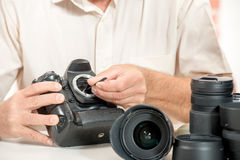 Close up of photographer hand cleaning sensor of his camera Royalty Free Stock Image