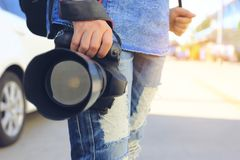 Close up of Photographer holding DSLR camera in his hands, Travel lifestyle vacations concept stock image