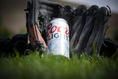 Close Up Photography of Coors Light Beer Near Black Baseball Mitts Royalty Free Stock Photography