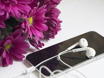 Close-Up Photography of Earphones on Top of Iphone 6 Near Flowers Royalty Free Stock Image