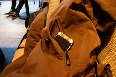 Beware of burglary. Close-up photography of a jacket layed uncautious with a view of a smartphone Stock Images