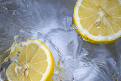 Close Up Photography of Two Lemon on the Water Sprinkled With Drops Stock Photo