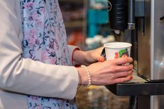 Close up photography. Women`s hands hold a colored paper glass w. Ith a hot drink Stock Images