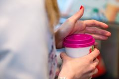 Close up photography. Women`s hands hold a colored paper glass w. Ith a hot drink Royalty Free Stock Images