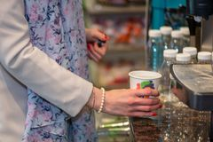 Close up photography. Women`s hands hold a colored paper glass w. Ith a hot drink Royalty Free Stock Photos
