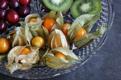 Close-up of Physalis fruit - Cape gooseberries with cranberries and kiwi royalty free stock image