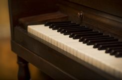 Close up of piano keys and old vintage wooden upright piano, shallow focus, warm brown tone royalty free stock image