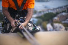 Close up pic of male rope access job industrial worker, using a safety device descender on static twin ropes abseiling, repairing. Windows at rise building in stock image
