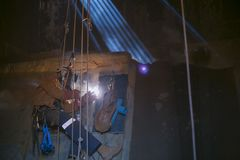 Close up pic rope access welder wearing safety equipment abseiling hanging on harness as fall arrest position welding repairs. Maintenance in confined space royalty free stock photos