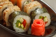 Close up pickled ginger in the form of red rose and sushi rolls. Hosomaki with vegetables, Uramaki with Conger on the background. Japanese cuisine. Shallow Stock Image