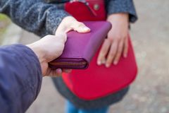 Close up pickpocketing outdoor. Close up picture of woman holding her red bag while a thief trying to steal from her Stock Photo