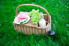 Close up of picnic basket with fruits and glass of wine on green Stock Photos