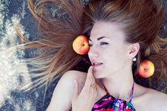 Close up picture of beautiful blond young woman sensual pretty girl with blue eyes lying with apples on stone rock or ice ground Stock Photo