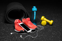Close-up of dumbbells, sports shoes, bottle for water and phone with handphones on a black floor background. Copy space. Royalty Free Stock Photos