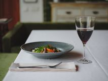 A dinner composition on a blurred restaurant background. A tasty dish next to a glass of red wine. Copy space. Royalty Free Stock Image