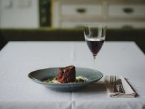 A dinner composition on a blurred restaurant background. A tasty dish next to a glass of red wine. Copy space. Stock Image