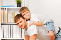 Close-up picture of boy riding on father's back Royalty Free Stock Photography