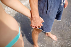 Close-up of boy and girl holding hands on the beach background. Young boyfriend and girlfriend. Teenage romance concept. Close-up picture of boyfriend and Stock Photo