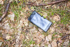 Close up picture of a broken mobile phone on a ground in park royalty free stock photography