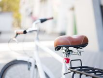 Close-up bicycle seat on a blurred background. Brown, retro bike seat. Modern transport. Copy space. Close-up picture of a brown skin bicycle seat on a blurred Royalty Free Stock Photography