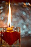 Close up Picture on the burning candle made from beeswax in the glass candle holder with red heart. Stock Photo