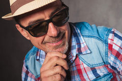 Close up picture of a casual man looking to side. Close up picture of an old casual man with hat and sunglasees looking to side away from the camera and smiles Royalty Free Stock Photography