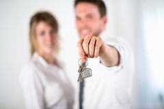 Close-up picture of cheerful young realtor couple holding house keys Royalty Free Stock Image